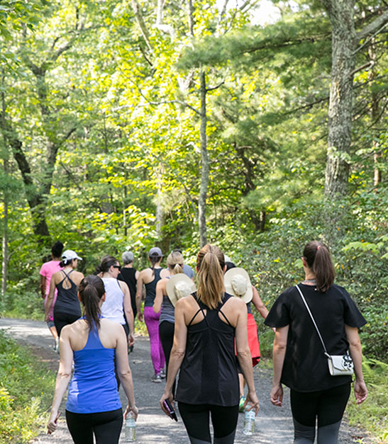 group of women walk on trail