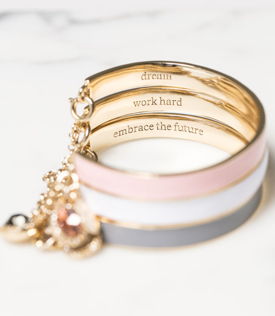 bracelet with engraved words that read dream, work hard, embrace the future