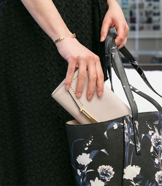 woman placing wallet into purse